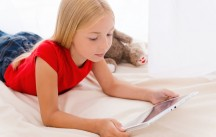 Playing on digital tablet. Cute little girl holding digital tablet and looking at it while lying in bed