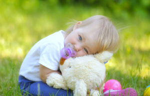 Cute baby with blue eyes hugging a mascot.