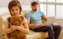 A sad little boy looking in camera and hugging a teddy bear, in the background his father using a laptop while sitting on a sofa without paying attention to his son.